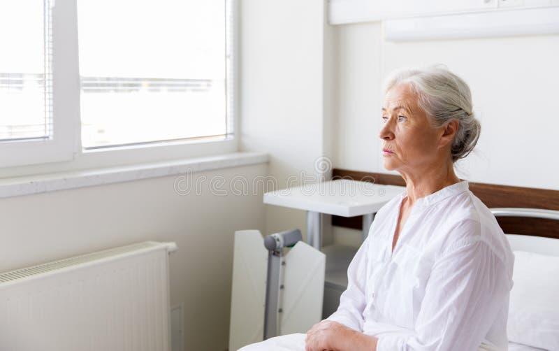 Mujer mayor triste que se sienta en cama en la sala de hospital fotos de archivo