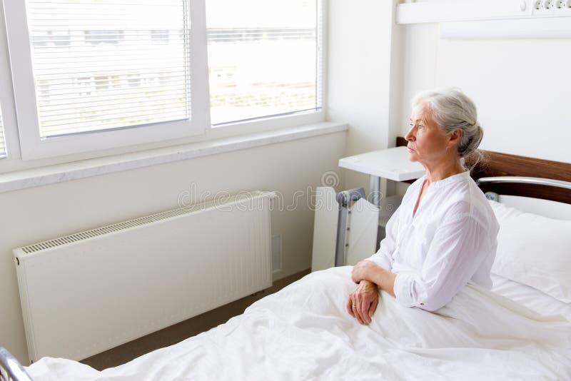 Mujer mayor triste que se sienta en cama en la sala de hospital imagenes de archivo