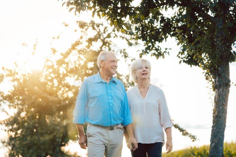 Mujer mayor y hombre que tienen un paseo a lo largo de la trayectoria en el campo imagen de archivo libre de regalías