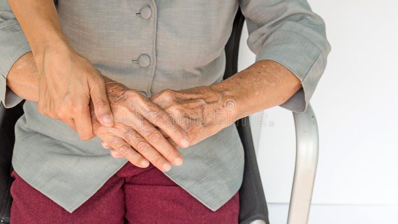mujer mayor y jóvenes que llevan a cabo las manos, la madre y el dauther fotografía de archivo