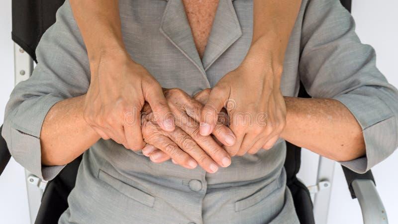 mujer mayor y jóvenes que llevan a cabo las manos, la madre y el dauther fotografía de archivo libre de regalías