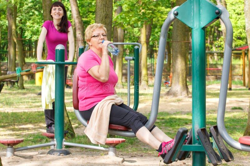 Mujer mayor y joven que ejercita la parte inferior del cuerpo en gimnasio al aire libre, forma de vida sana fotografía de archivo