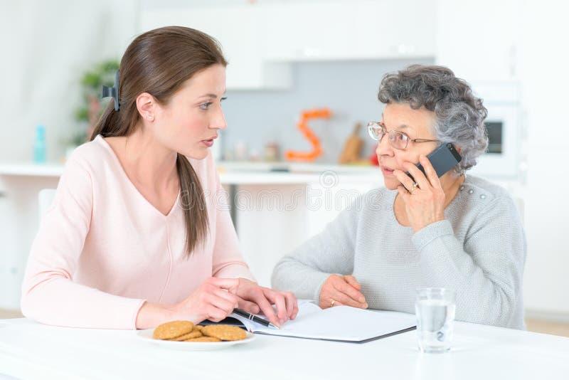 Mujer mayor y mujer joven en el teléfono imagen de archivo