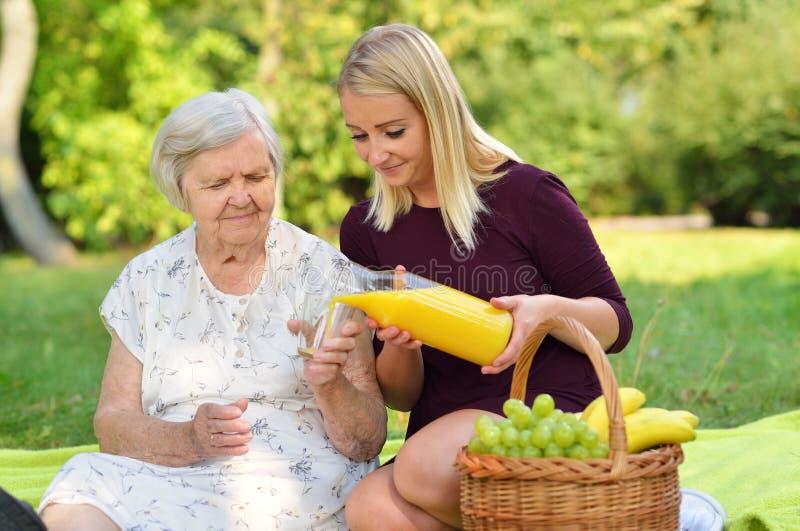 Mujer mayor y mujer joven en la comida campestre imagen de archivo