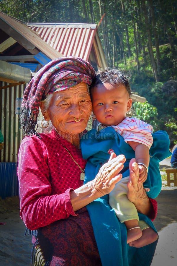Mujer mayor y niño joven junto en un pueblo de montaña, Nepal imagenes de archivo