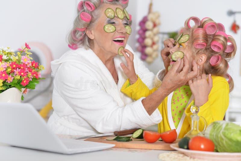 Mujer mayor y nieta que hacen máscaras faciales en la cocina imagen de archivo