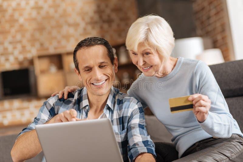 Mujer mayor y su hijo que hacen hacer compras en línea junto foto de archivo libre de regalías
