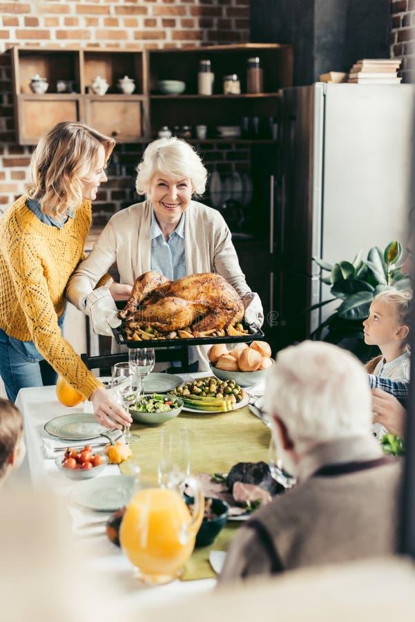 mujer mayor y su pavo que lleva de la hija para la cena de la acción de gracias con su fotos de archivo