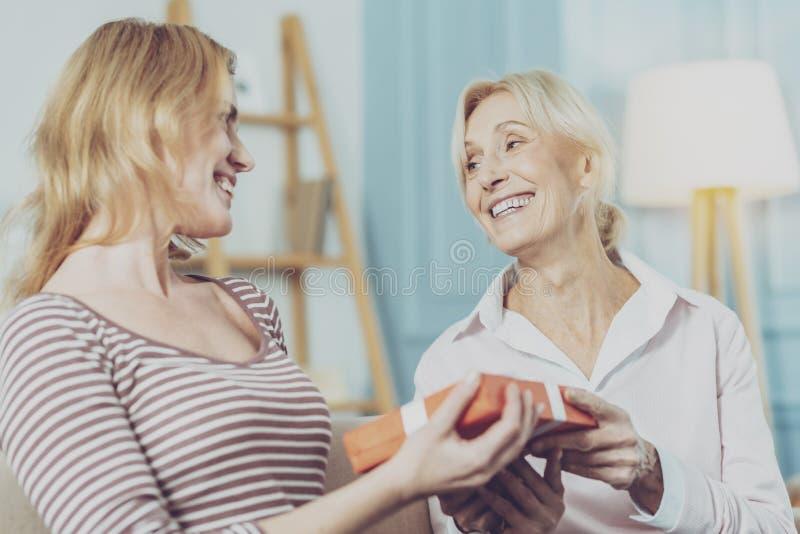 Mujer mayor y su situación de la hija con un regalo foto de archivo libre de regalías