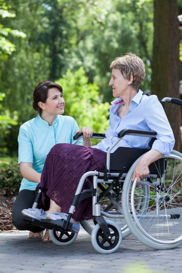 Mujer mayor y una enfermera que sonríe junto foto de archivo