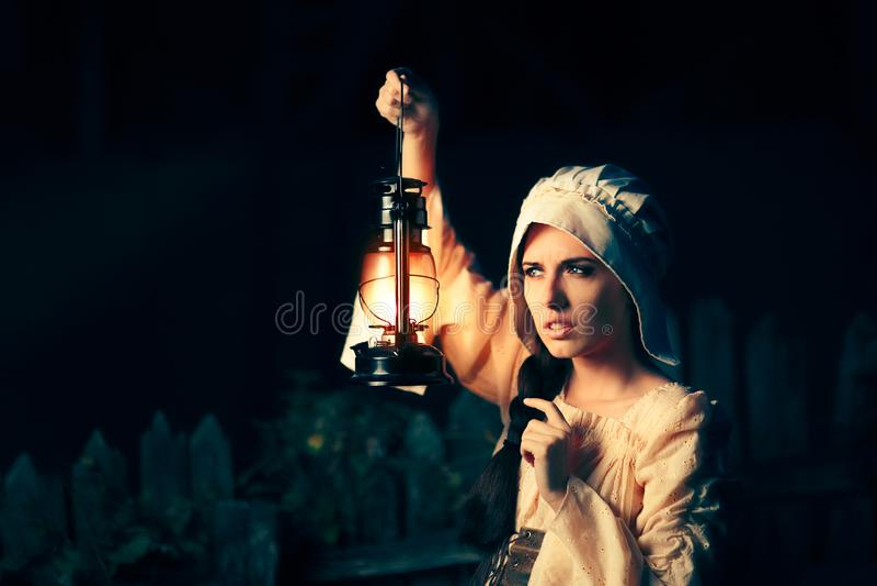 Mujer medieval curiosa con la linterna del vintage afuera en la noche imagen de archivo