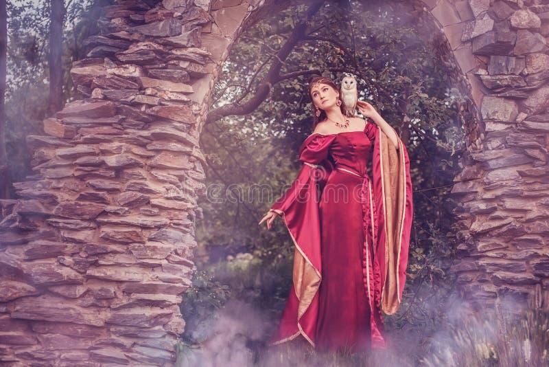Mujer medieval hermosa, con una lechuza común en su hombro foto de archivo