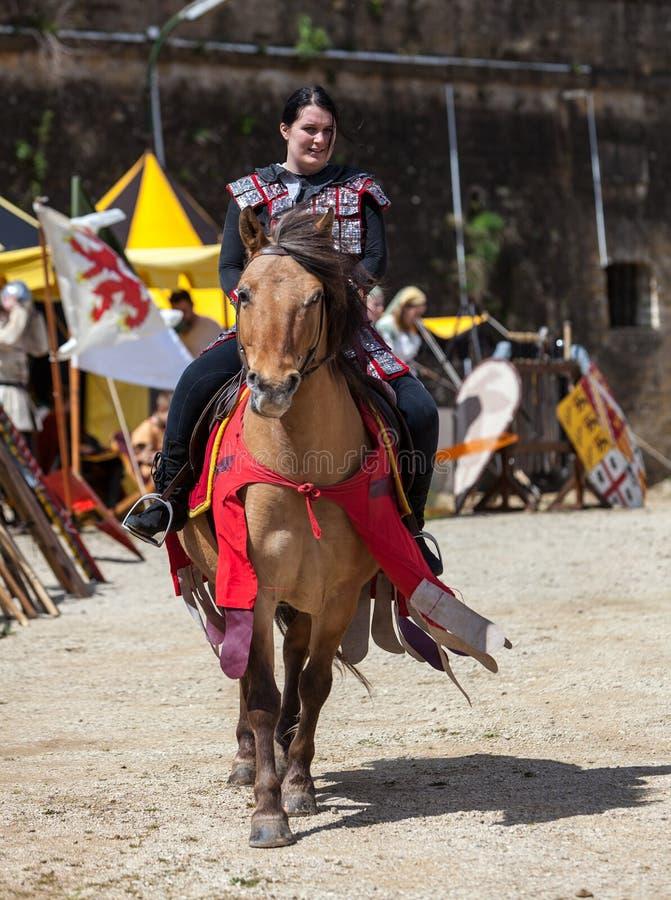 Mujer medieval que monta un caballo imagenes de archivo