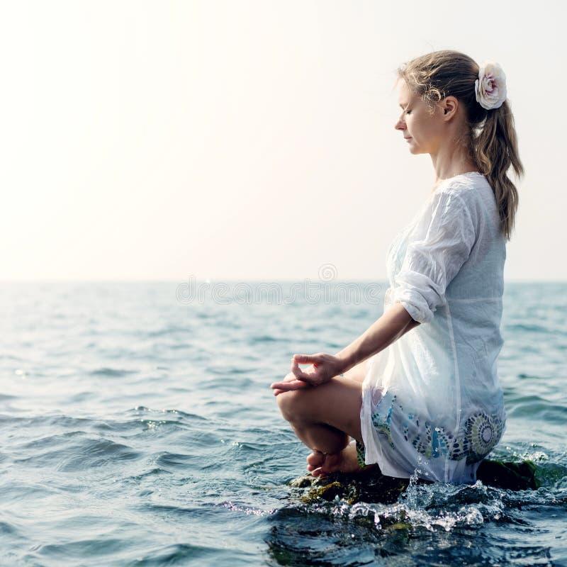 Mujer meditating en el mar fotos de archivo libres de regalías