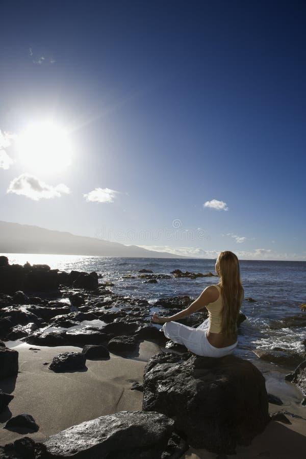 Mujer meditating en la playa imágenes de archivo libres de regalías