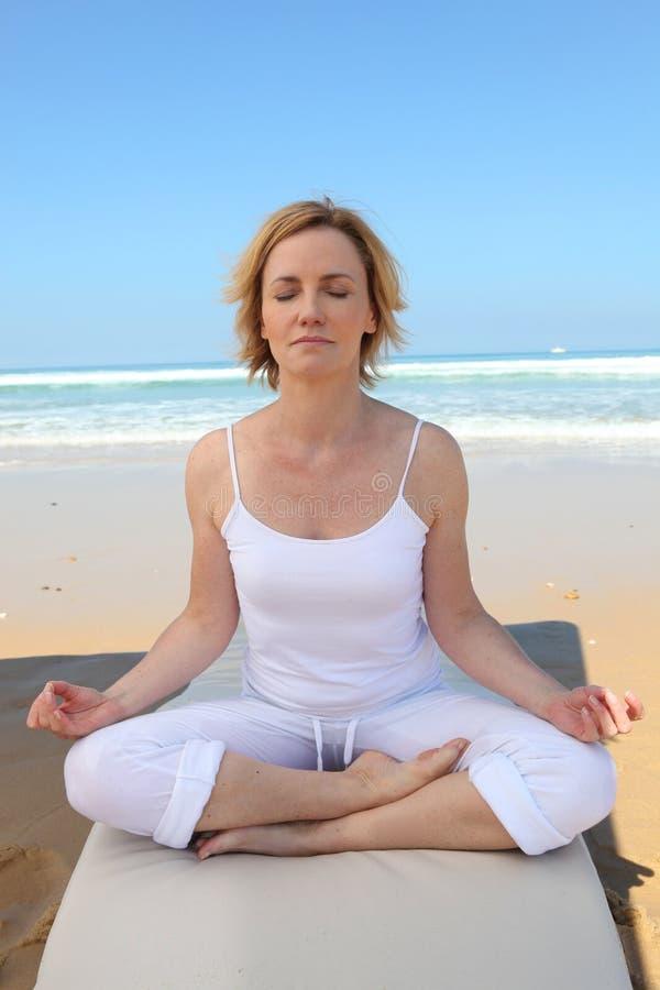 Mujer meditating en la playa foto de archivo libre de regalías
