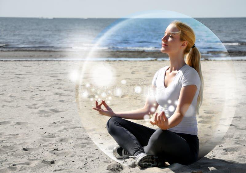 Mujer Meditating en la playa en paz imagen de archivo