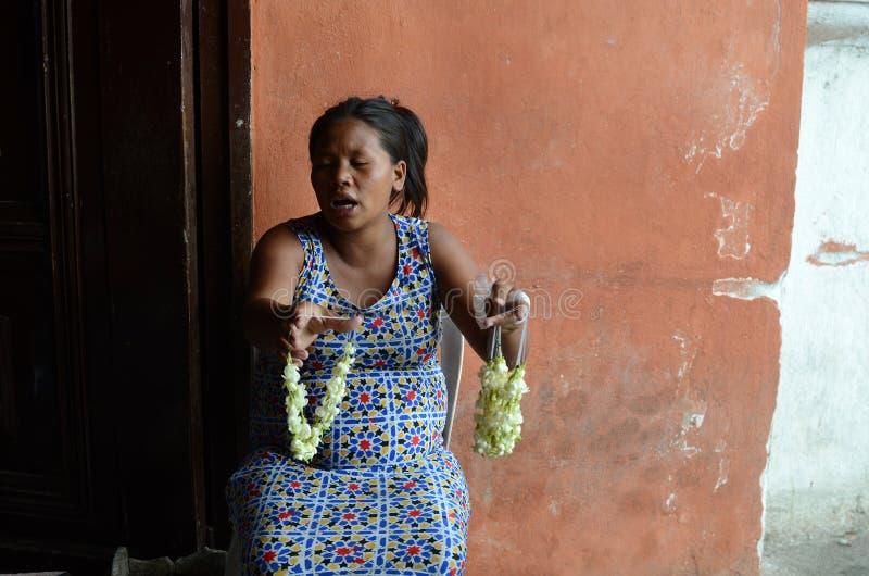 mujer mendigante que vende las flores del sampaguita en el portal de la iglesia fotos de archivo libres de regalías
