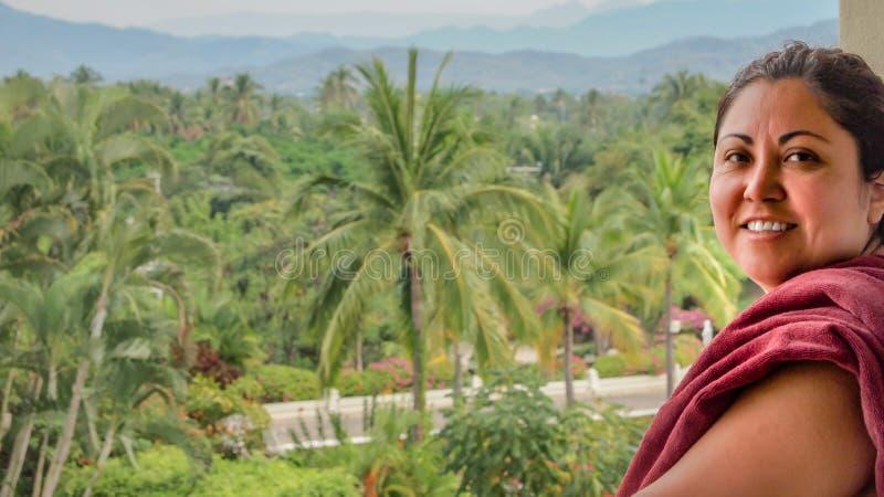 Mujer mexicana hermosa que está en un balcón con las palmeras y las montañas en el fondo foto de archivo libre de regalías