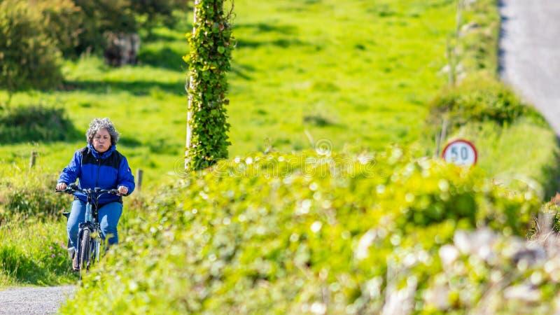 Mujer mexicana madura cansada que monta su bicicleta entre los prados de una colina fotos de archivo