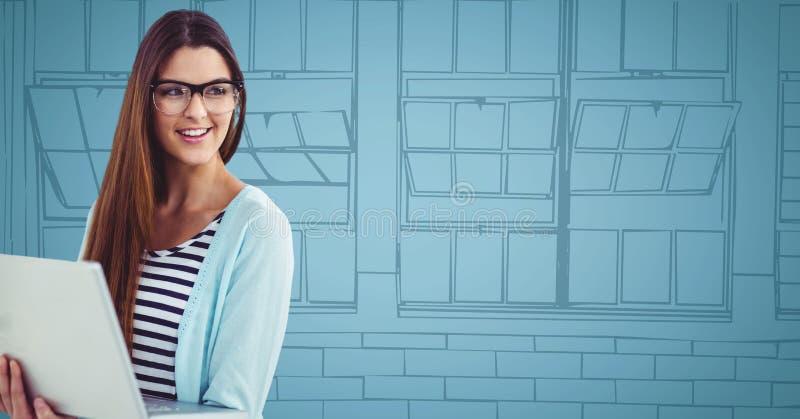 Mujer milenaria con el ordenador portátil contra ventanas dibujadas mano azul foto de archivo