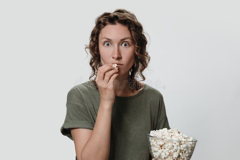 Mujer milenaria joven con el pelo rizado que come las palomitas, mirando una pel?cula o a programas de televisi?n fotografía de archivo