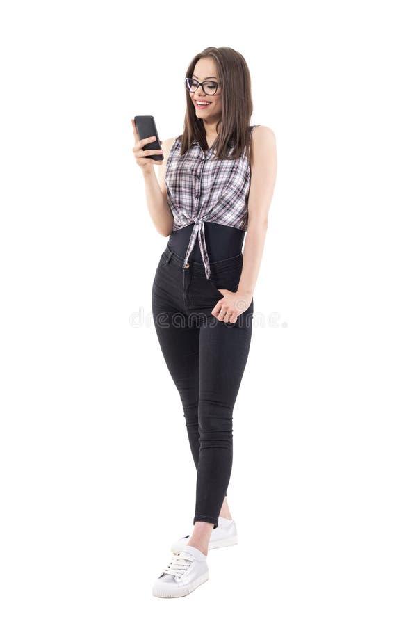 Mujer milenaria joven de moda que sostiene el teléfono móvil que practica surf la red y la sonrisa imagenes de archivo