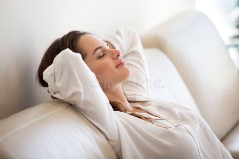 Mujer milenaria tranquila que se relaja en fre de respiración del sofá cómodo foto de archivo
