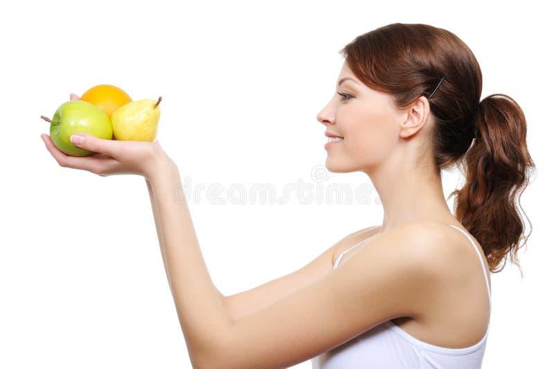 Mujer mirando ay las frutas imagen de archivo libre de regalías
