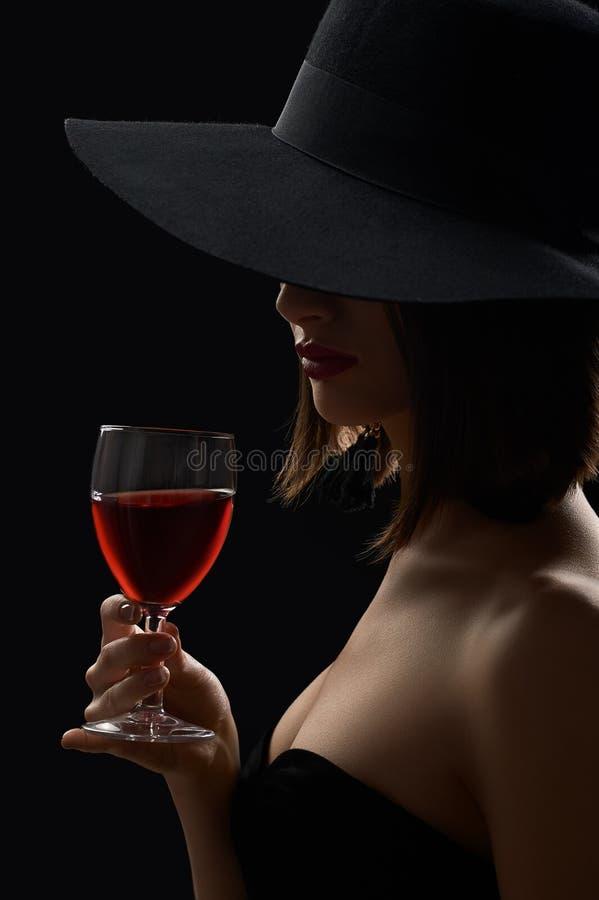 Mujer misteriosa elegante en un sombrero que sostiene un vidrio de vino rojo encendido fotos de archivo libres de regalías