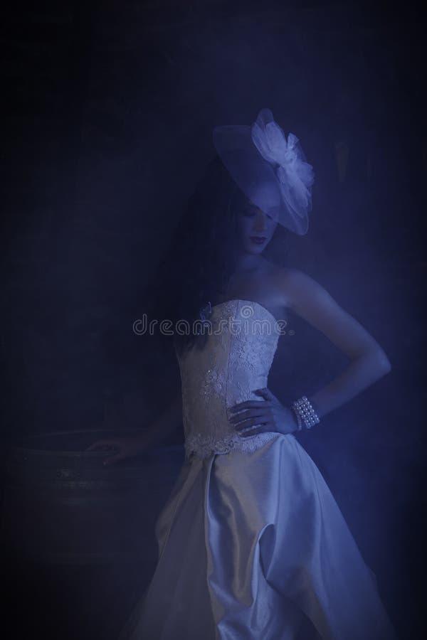 Mujer misteriosa en el vestido de boda rodeado por la neblina ahumada azul fotografía de archivo