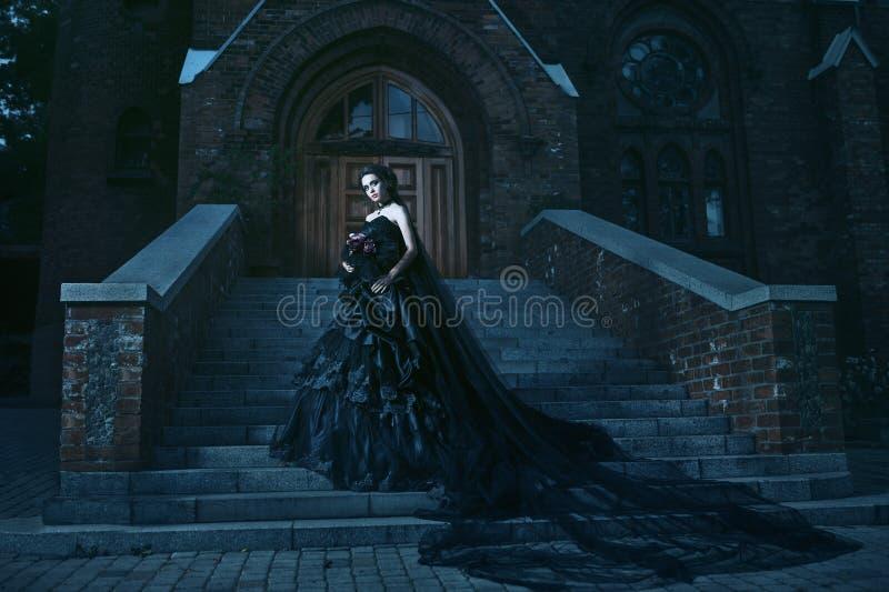 Mujer misteriosa en vestido negro cerca del chirch imagen de archivo libre de regalías