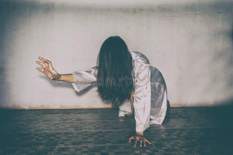 Mujer misteriosa, escena del horror de la mujer asustadiza del fantasma que sostiene la muñeca fotos de archivo