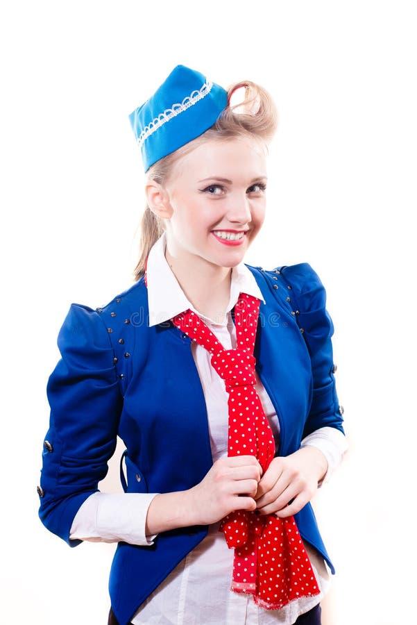 Mujer modela rubia joven del asistente de vuelo con los bigudíes en la chaqueta azul y el casquillo, sonrisa feliz de la bufanda  fotos de archivo libres de regalías