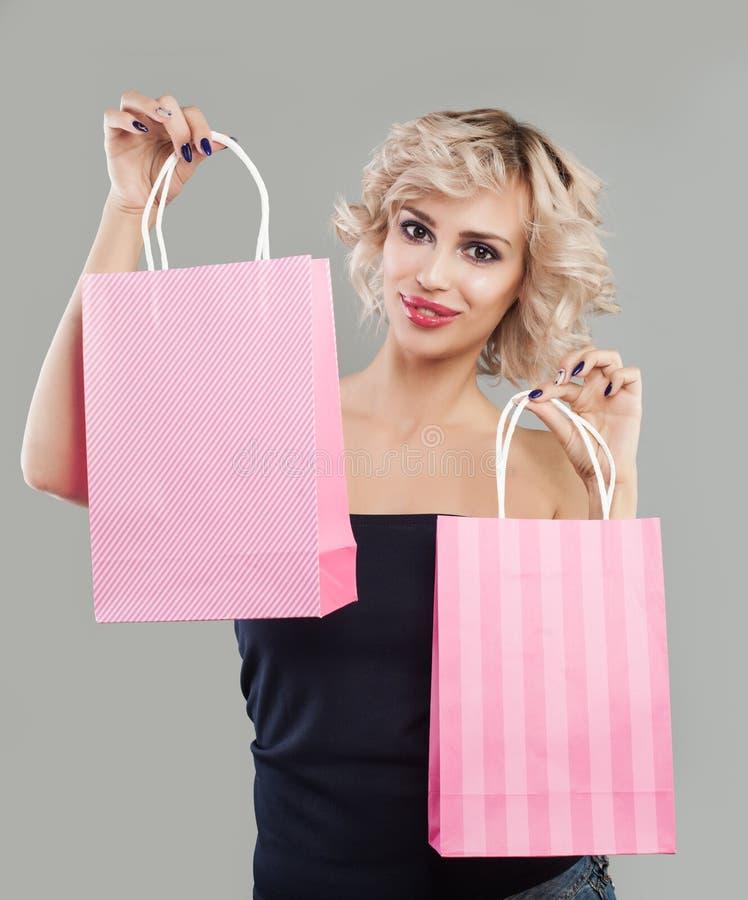Mujer modelo bonita que muestra dos bolsos que hacen compras y sonrisas rosados imagen de archivo