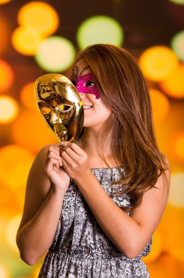 Mujer modelo de la belleza que lleva la máscara rosada del carnaval con una máscara del oro en sus manos foto de archivo