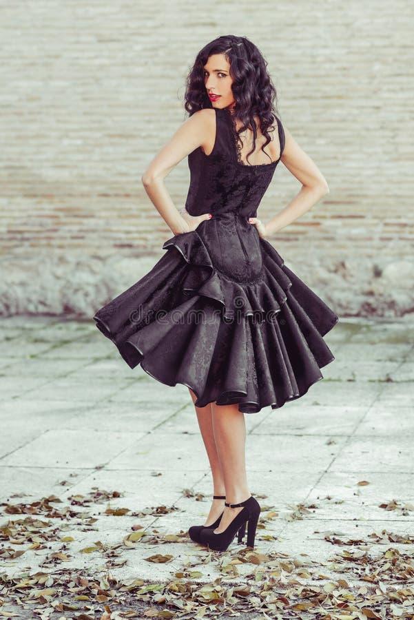 Mujer, modelo de la moda, vestido negro que lleva con el pelo rizado fotos de archivo libres de regalías