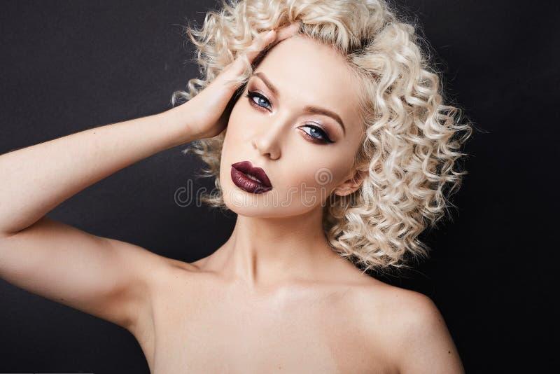 Mujer modelo elegante con los ojos azules maravillosos y con el pelo rizado rubio, con los labios llenos y el maquillaje brillant fotografía de archivo libre de regalías