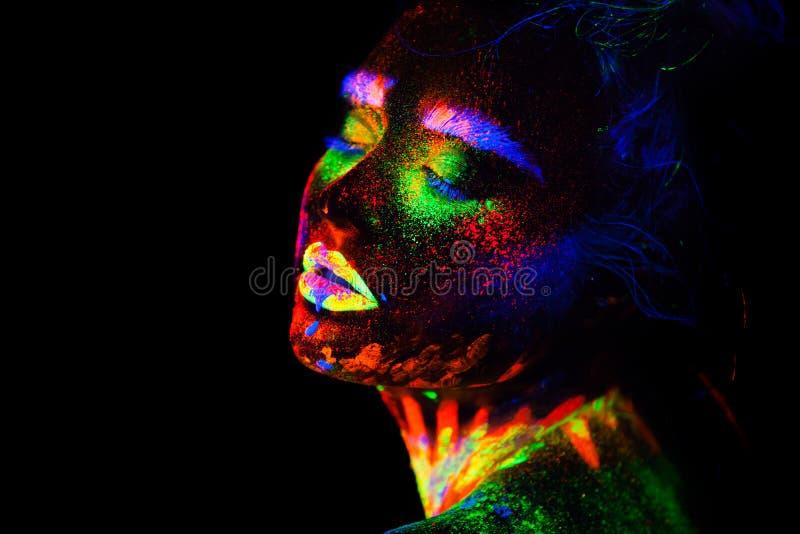 Mujer modelo extraterrestre hermosa en la luz de neón Es retrato del modelo hermoso con el maquillaje fluorescente, arte fotos de archivo