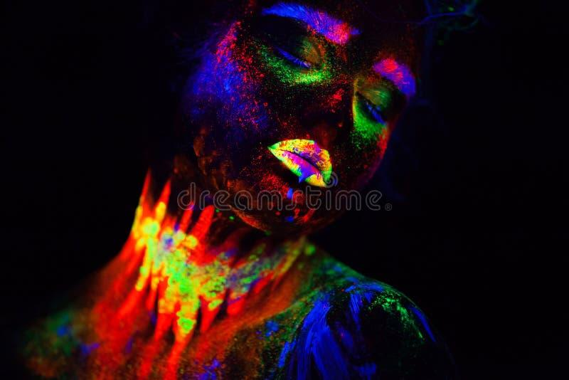 Mujer modelo extraterrestre hermosa en la luz de neón Es retrato del modelo hermoso con el maquillaje fluorescente, arte foto de archivo