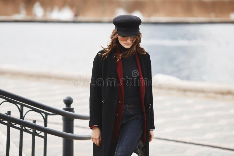 Mujer modelo hermosa y de moda, en el casquillo, la capa y las gafas de sol, presentando en el paisaje urbano imagenes de archivo