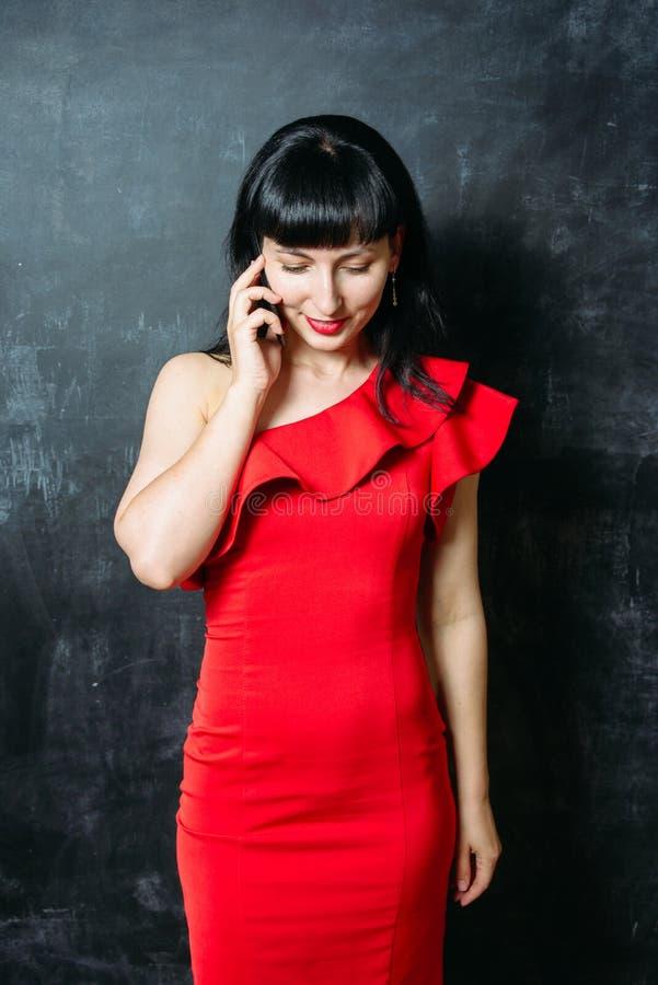 Mujer modelo joven hermosa en el vestido rojo que presenta sobre pizarra negra fotografía de archivo