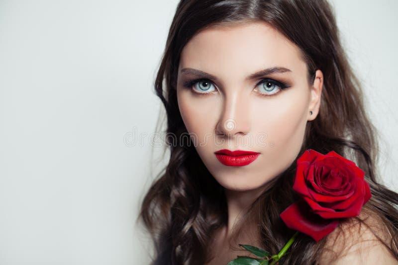 Mujer modelo linda con el maquillaje rojo de los labios que sostiene la flor color de rosa roja fotos de archivo