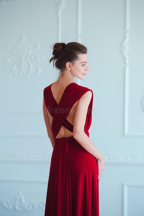 Mujer modelo morena de la belleza en la igualación del vestido rojo Maquillaje de lujo y peinado de la moda hermosa Muchacha atra foto de archivo