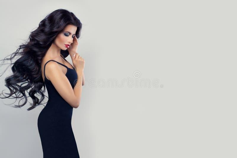 Mujer modelo morena hermosa con el pelo perfecto largo en vestido negro contra el fondo blanco de la pared fotos de archivo