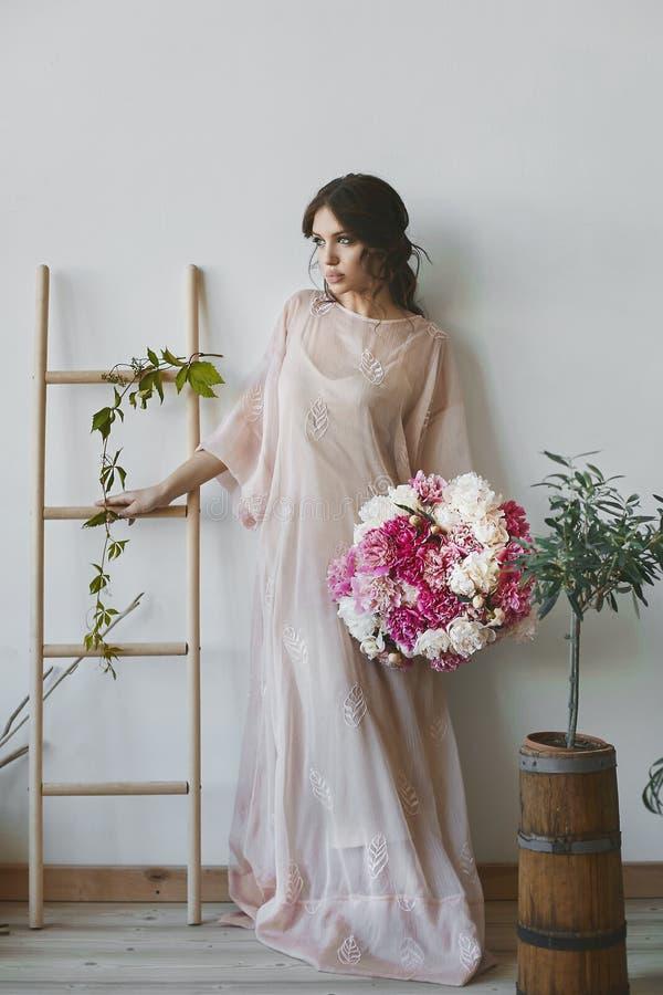 Mujer modelo morena hermosa con los labios llenos atractivos y con los ojos azules en un vestido largo de moda que sostiene un gr fotos de archivo libres de regalías