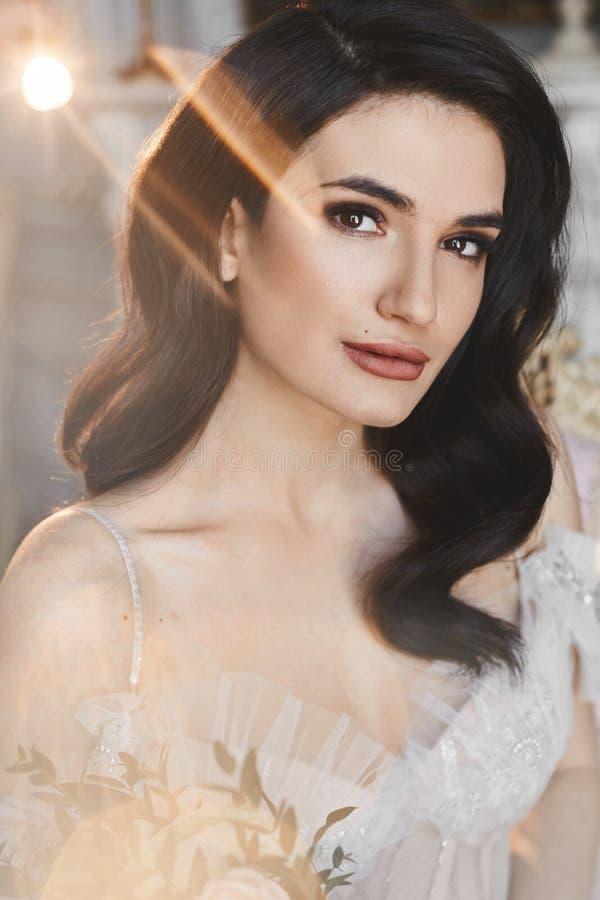 Mujer modelo morena hermosa con los labios llenos y maquillaje desnudo en vestido elegante del cordón en el interior de lujo del  fotografía de archivo libre de regalías
