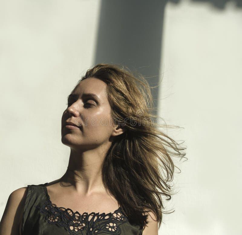Mujer modelo profesional atractiva y hermosa joven que presenta el vestido costoso del dise?o que lleva con el pelo rubio que vue fotografía de archivo