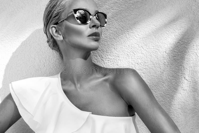 Mujer modelo rubia atractiva elegante imponente fenomenal hermosa del retrato con llevar perfecto de la cara gafas de sol e inter fotografía de archivo libre de regalías