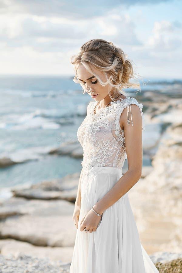 Mujer modelo rubia joven hermosa con maquillaje desnudo en un vestido que se casa de moda que camina en la costa de mar en Chipre fotografía de archivo